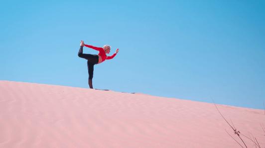 砂漠でヨガをする女