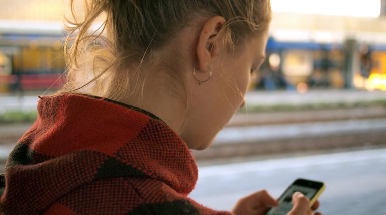 携帯を触っている女性の後ろ姿