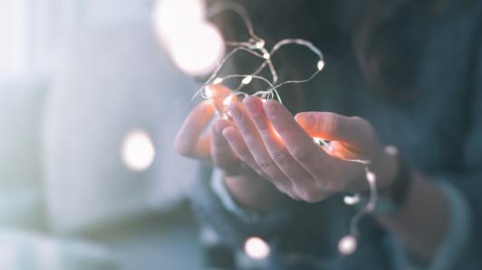 女性の手に絡み付いた電球